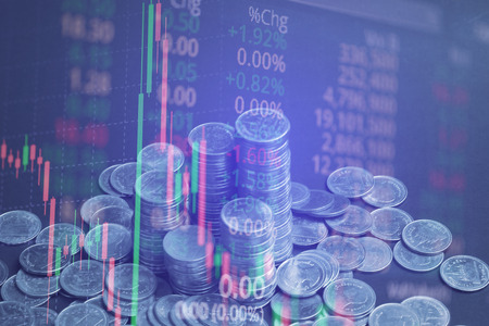 Double exposure of coin stack with stock market screen chart board and candle stick for financial business and investor analysis concept idea.