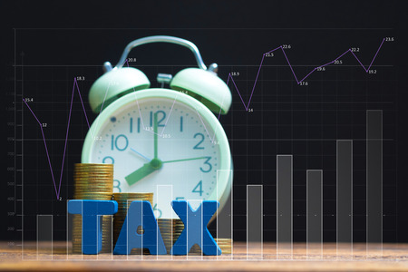 Time to pay TAX concept. TAX alphabet with stack of coin and vintage alarm clock with financial graph,, business and financial concept idea.