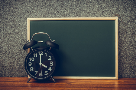 Black vintage alarm clock with green chalkboard, copy space for add your text, work on time or over time and deadline concept idea. Фото со стока