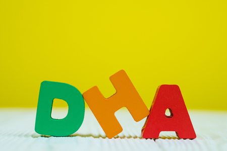 DHA text alphabet on white wooden table. yellow wall background with copy space for add text. Stok Fotoğraf