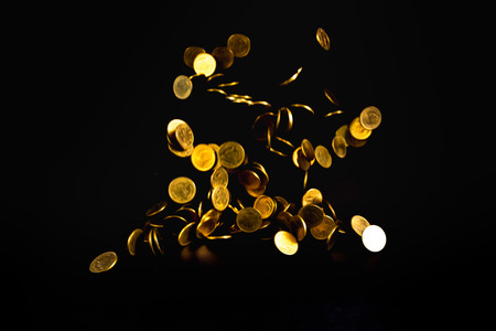Falling gold coins money in dark background, business concept idea.
