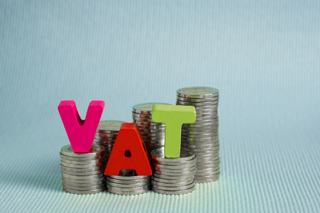 VAT (Value Added Tax) concept. Word VAT alphabet made from wood with stack of coin, business and financial concept idea.