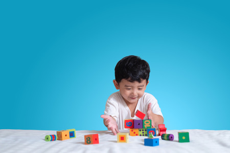 3 years old little cute Asian boy play toy or square block puzzle at home on the bed, kid lying learn by playing block shape or pieces, education and healthy concept.
