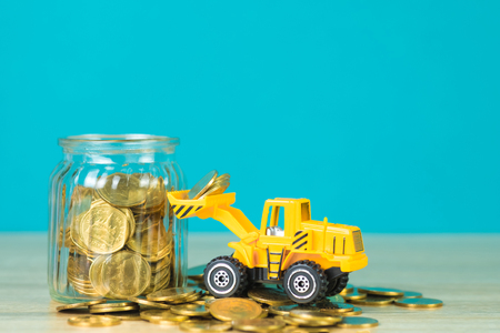 Mini bulldozer truck loading stack coin with pile of gold coin to glass jar, business finance and banking industrial concept idea.