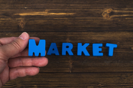 Hand and finger arrange text letters of MARKET word on wood table, with copy space for add advertising word or product. business and finance concept idea.