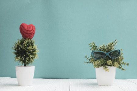 Blue sunglasses with little decoration tree in white vase and red heart on white wood and green background, hello weekend vacation travel concept.