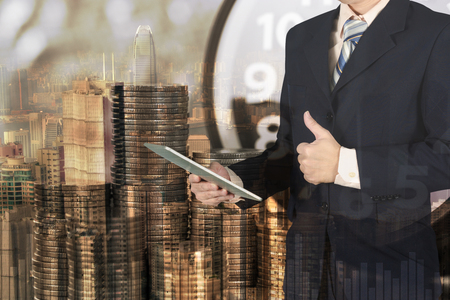 Double exposure of alarm clock and coins stacks with city background businessman and finance graph, time for savings money concept, banking and business concept idea.