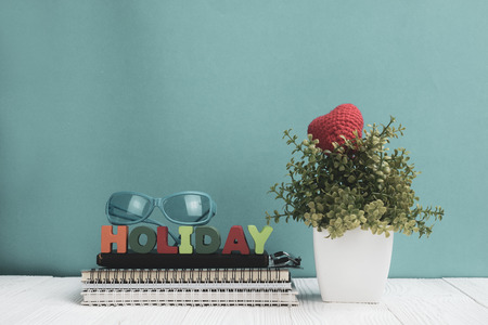 HOLIDAY letters text and notebook paper and little decoration tree in white vase on wooden background, hello weekend vacation concept idea. Stock Photo