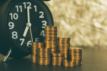 Alarm clock and coins stacks on working table, time for savings money concept, banking and business concept idea.