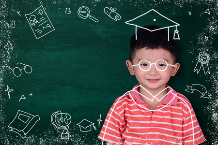 Asian kid imagine his graduated day with hand drawn graduate dress and stationery supplies school object activities for learning on green chalkboard background, education and graduation concept idea.