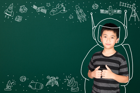 Asian kid with his imagination about science and space adventure, hand drawn on the green chalkboard, education back to school and discovery concept idea.