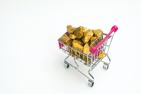 Pile of gold nuggets or gold ore in shopping cart or supermarket trolley on white  background, precious stone or lump of golden stone, financial and business concept idea. Stock Photo