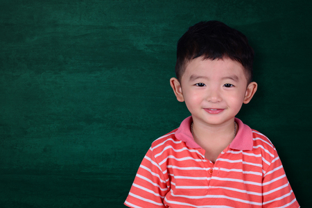 Happy Asian kid smiling on empty green chalkboard with copy space for add text or word, education and back to school concept idea.