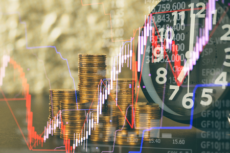 Double exposure of alarm clock and coins stacks with candle stick and stock market price screen, time for savings money concept, banking and business concept idea.