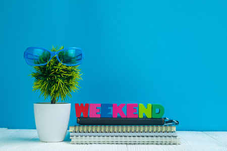 WEEKEND letters text and notebook paper and little decoration tree in white vase on wooden background, hello weekend vacation concept idea. Stock Photo