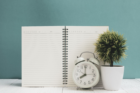 Office supplies or office work essential tools items on wooden desk in workplace, notebook, alarm clock and little tree with green wall background copy space Stock Photo
