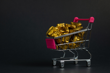 A pile of gold nuggets or gold ore in shopping cart or supermarket trolley on black background, precious stone or lump of golden stone, financial and business concept idea.