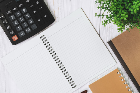 Fountain pen or ink pen with notebook paper and calculator on wooden working table with copy space, office desk concept idea. top view. Stock Photo