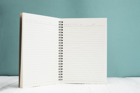 Blank notebook on white wood table front green wall background with copy space for add text or advertising word, menu mockup.