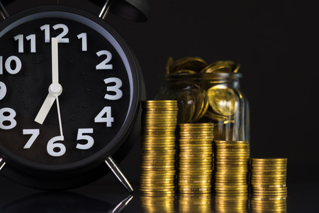 Coins stacks with coin in glass jar bottle and alarm clock in dark room, business and finance concept idea.
