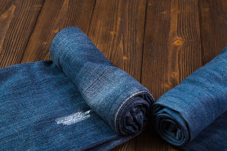 Roll Frayed jeans or blue jeans denim collection on rough dark wooden table background with copy space, old fashion style concept.