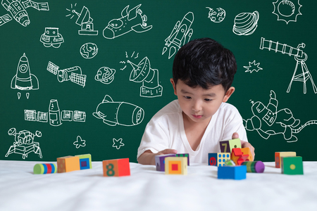 Asian kid learning by playing with his imagination about science and space adventure, hand drawn on the green chalkboard, education back to school and discovery concept idea.