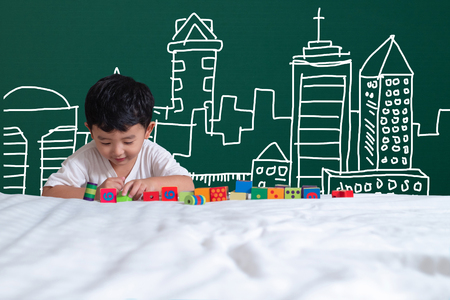 Asian kid learning by playing with his imagination about building and engineer architecture drawing and designer, hand drawn on the green chalkboard, education back to school concept idea.