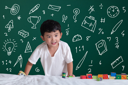 Asian kid learning by playing with his imagination about stationery supplies school object activities for learning, hand drawn on the green chalkboard, education back to school concept idea.