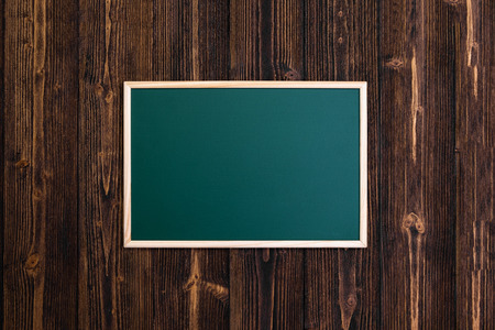 Empty green chalkboard with wooden frame on wooden desk, top view with copy space for add text and message.