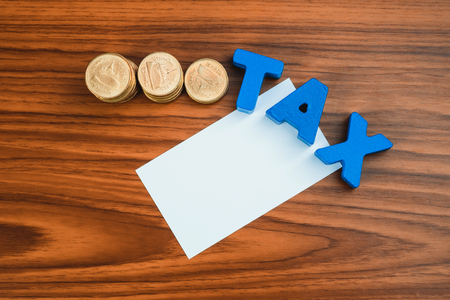 TAX concept. TAX alphabet with stack of coin and business card or name card on wooden working table, business and financial concept idea.