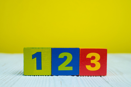 Square block puzzle number 1 2 and 3 on table with yellow wall background