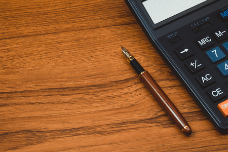 Fountain pen or ink pen with calculator on wooden working table with copy space, office desk concept idea.