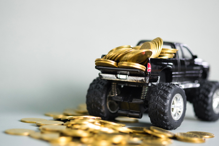 Black colour of miniature car pickup truck with stacks of coins on grey background with copy space, banking savings money and business finance concept.