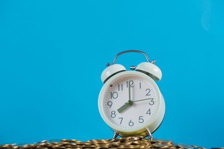 Vintage alarm clock on the pile of gold coin with blue background, time and business finance concept idea.