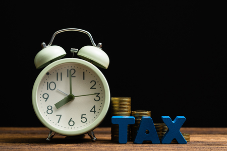 Time to pay TAX concept. TAX alphabet with stack of coin and vintage alarm clock on wooden working table in dark background, business and financial concept idea. Standard-Bild
