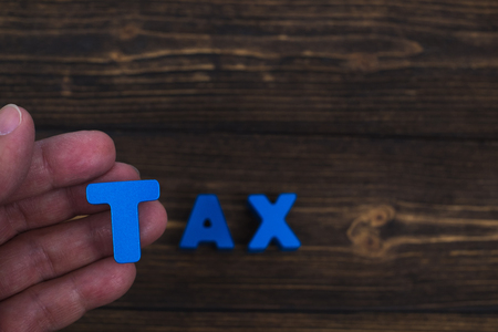 Hand and finger arrange text letters of TAX word on wood table, with copy space for add advertising word or product. business and finance pay tax concept idea.