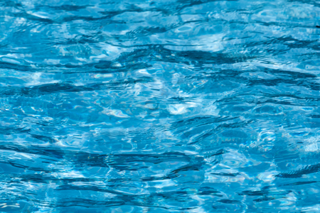 Blue and bright ripple clean water surface in swimming pool with sun reflection.