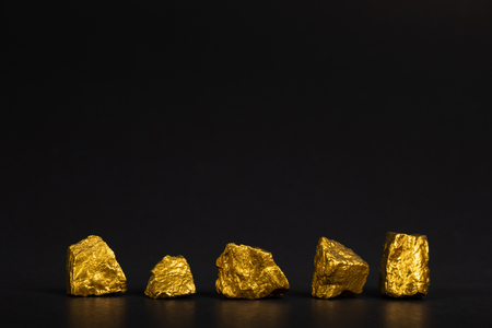A pile of gold nuggets or gold ore on black background, precious stone or lump of golden stone, financial and business concept idea. Reklamní fotografie