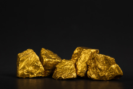 A pile of gold nuggets or gold ore on black background, precious stone or lump of golden stone, financial and business concept idea. Stock Photo
