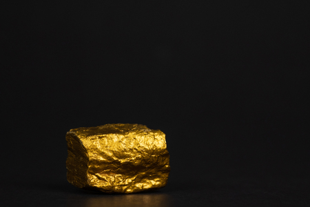 Closeup of gold nugget or gold ore on black background, precious stone or lump of golden stone, financial and business concept idea. Stock Photo
