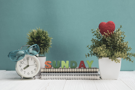 SUNDAY letters text and notebook paper, alarm clock and little decoration tree in white vase on wooden table, hello Sunday weekend concept idea. 스톡 콘텐츠