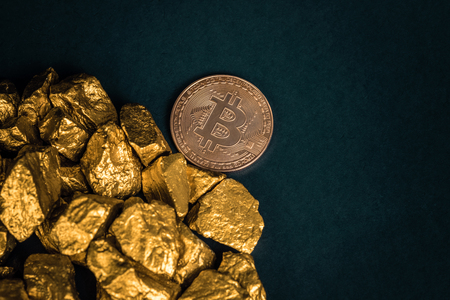 Closeup of bitcoin digital currency and gold nugget or gold ore on black background, precious stone or lump of golden stone, Cryptocurrency money financial and business concept idea.