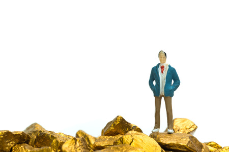 Figure miniature businessman or small people with pile of gold nuggets or gold ore on white background, precious stone or lump of golden stone, financial and business concept idea.