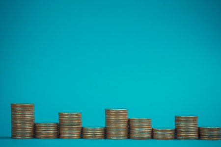 Columns of coins, piles of coins on blue background, business and financial concept idea.