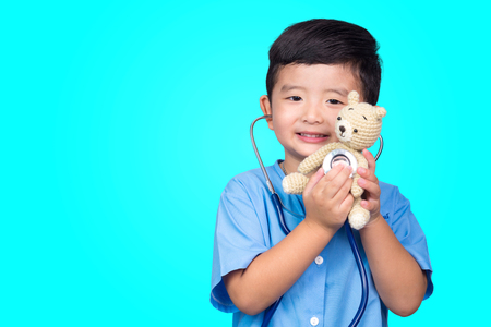 Smiling Asian kid in blue medical uniform holding stethoscope looking at camera on blue green background with copy space, healthy concept idea.