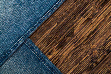 Frayed jeans or blue jeans denim collection on rough dark wooden table background, top view with copy space, old fashion style concept. 免版税图像