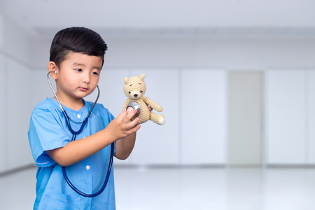 Smiling Asian kid in blue medical uniform holding stethoscope looking at camera, healthy concept idea. Standard-Bild