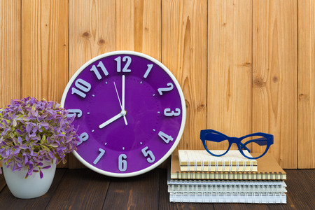 Office supplies or office work essential tools items, notebook and alarm clock with little tree and glasses on the wood. 스톡 콘텐츠