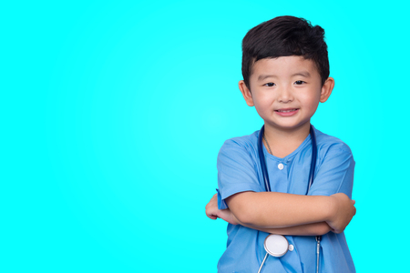 Smiling Asian kid in blue medical uniform holding stethoscope looking at camera on blue green background with copy space, healthy concept idea. Stock fotó