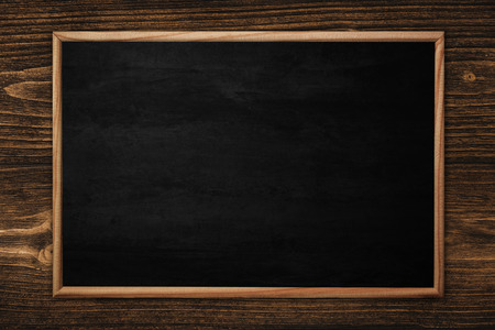 Abstract blackboard or chalkboard with frame on wooden background. empty space for add text. Banco de Imagens